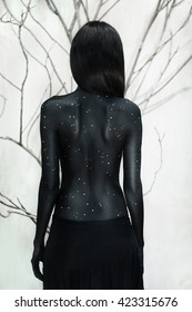 Mysterious woman portrait with branches background. Body art with moon and stars. Back view. Space for text.