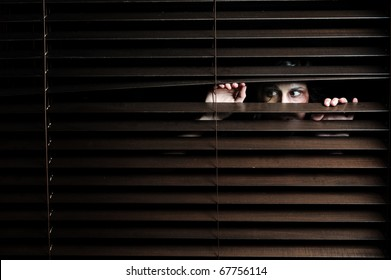 Mysterious woman pulls the blinds apart to see the outside world