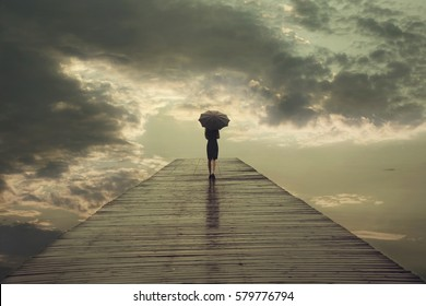 mysterious woman with umbrella crosses a bridge to the threatening sky