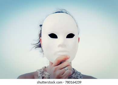 A mysterious woman wearing a lifeless white mask. Close-up symbolic shot. Outdoors, blue sky. Secrets, mystery, unknown.