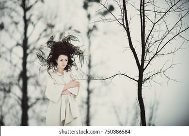 Mysterious woman in white dress with fairy tale hair-do stands in winter forest