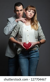 Mysterious young couple in love holding red heart.