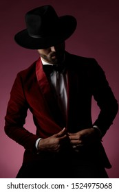 mysterious young man wearing red velvet tuxedo and hat, arranging coat and looking down, on pink background in studio