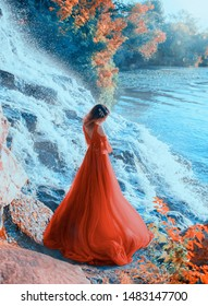 A mysterious young sad woman stands on the riverbank near a waterfall, in a red, long dress and dreams. Background autumn landscape, yellowed trees. Shooting from the back, without a face, rear view.