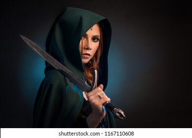 Mysterious young woman keeping sharp knife, wearing green cape with a hood, saturated evening make up. Model looking at camera, having brown hair, big eyes, plump lips. Studio background.