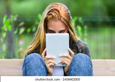 Mysterious young woman peering over a tablet-pc with just her eyes visible over the tom as she sits with her feet up and knees bent on a bench outdoors