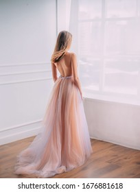 Mysterious young woman princess in elegant beautiful airy luxury long evening trendy dress, bare open back. Sexy Girl graduate prom blond hair fly wind. turned away look window room Glamour fashion
