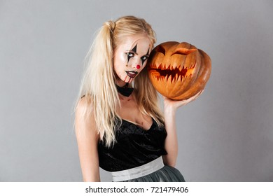 Mystery blonde woman in halloween make up posing with carved pumpkin and looking at the camera over gray background