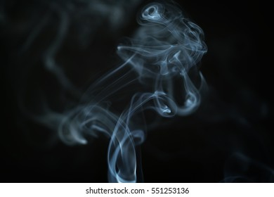 mystery blue smoke over dark background closeup, shallow focus