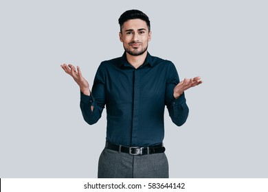 Mystery!  Confused young man shrugging shoulders and making face while standing against grey background