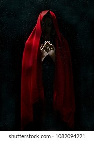A Mystery in the Dark. This picture shows a mysterious image of a woman standing the dark covered with a red veil. She appears to be something of a supernatural creature.