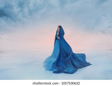 Mystery fantasy Woman Snow Queen blue raincoat cape hood flutters waving fly wind. traveler background sunrise sunset winter frozen valley covered snow blue white dramatic sky clouds heaven princess
