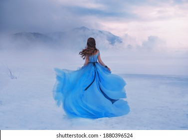 Mystery fantasy Woman Snow Queen in blue lush dress, fly in wind. Lady traveler. Art background winter frozen nature mountains, snow white dramatic sky clouds heaven. Girl princess walks, back view.