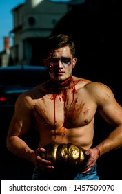 Mystery and horror concept. Big zombie man halloween vampire or bloody war soldier with wounds and red blood with pumpkin. Halloween face art. Strong man body. Half face portrait. Hot guy. Fitnes