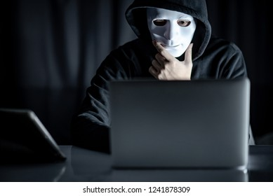 Mystery male hoodie hacker holding white mask looking at laptop computer. Anonymous social masking. Ransomware cyber attack or internet security concepts