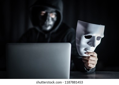 Mystery male hoodie hacker wearing black mask holding white mask with laptop computer on the table. Anonymous social masking. Ransomware cyber attack or internet security concepts