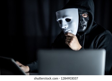 Mystery male hoodie hacker wearing black mask holding white mask sitting with laptop computer on the table. Anonymous social masking. Ransomware cyber attack or internet security concepts