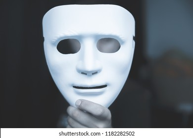 Mystery man holding white mask.