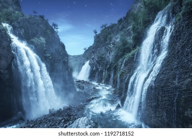 Mystery night at deep tropical forest with flowing cascade waterfall. Fantasy landscape