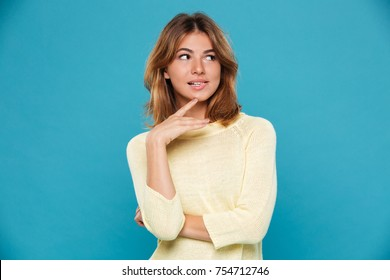 Mystery playful woman in sweater bites her lip and looking away over blue background