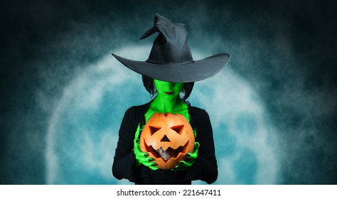 Mystery witch with green skin holds Halloween pumpkin with gray rat at midnight