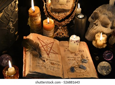 Mystic background with old book, skull, candles and mirror. Halloween and occult concept, black magic ritual. There is no foreign text in the image, all symbols are imaginary and fantasy ones