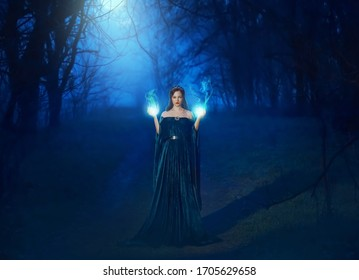 Mystic beauty woman evil witch in dark night fog forest blue moon light. Hands burning magic spell fire. Vampire queen demon power face. Vintage medieval dress cape. Scary Lady Halloween style clothes