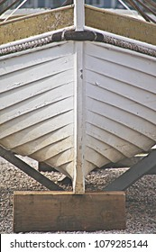 Mystic, Connecticut/USA- December 11, 2015: vertical closeup of the dry docked bow of a white skiff at a boat dock in a local marina.