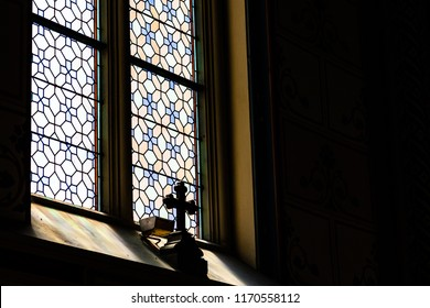 Mystic cross in the shadow in front of the stained transparent glass in a  gothic catholic cathedral