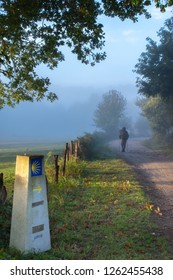 Mystic fog in the morning on the Camino de Santiago in Galicia. Beautiful and magic atmosphere. Pilgrim man walking by the path and around a touristic sign of scallop shell of the camino.