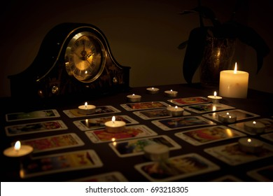 Mystic fortune-telling with fired candles and playing cards in d