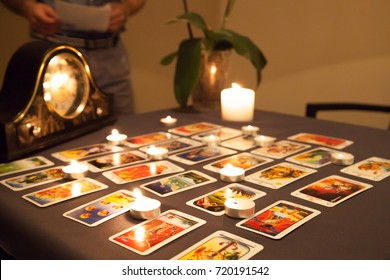Mystic fortune-telling with fired candles and playing cards on  dark background