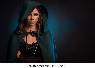 Mystic girl posing on dark studio background, wearing green cape, black corset. Model looking ar camera, having big eyes, brown curly hair. Looking like musterious elf queen.