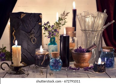 Mystic objects, black candles, magic book and glass bottles on planks. Alternative medicine, old pharmaceutic and homeopathic concept. Mystic and occult still life, vintage medical background