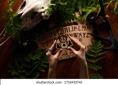 Mystic ritual with Ouija and candles. Devil's board concept, black magic or fortune telling rite with occult and esoteric symbols. Mystical rituals and occult sciences.