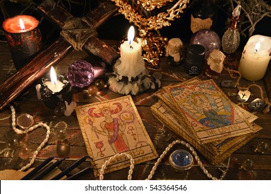 Mystic ritual with tarot cards, vintage objects, cross and candles. Halloween concept, black magic or fortune telling rite with occult and esoteric symbols. Astrology divination theme