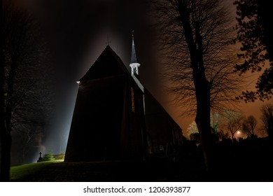 """mystic scene with the silhouette of the graveyard and church """"St. Bartholomaeus"""" in Golzwarden, Germany at night, it is enlightened by strong floodlights that reflect in the misty or foggy air"""