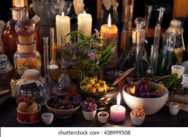 Mystic still life with dry herbs, old bottles, candles and flasks. Old pharmacy, esoteric or alchemic concept. Black magic and occult objects, alternative medicine or homeopathic still life