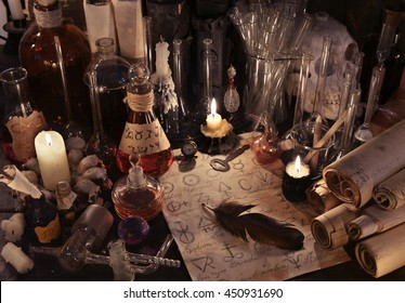 Mystic still life with scrolls, vintage bottles, candles, skull and magic objects. Old pharmacy or witch laboratory. There is no foreign text in the image, all symbols are imaginary and fantasy ones.