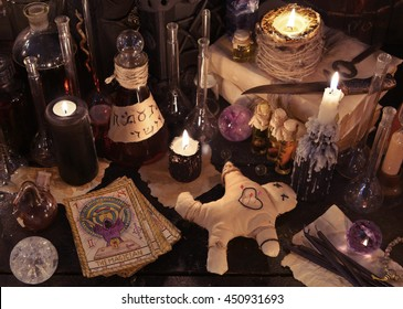 Mystic still life with voodoo doll, the tarot cards, books, evil candles and witchcraft objects. Divination rite. There is no foreign text in the image, all symbols are imaginary and fantasy ones.