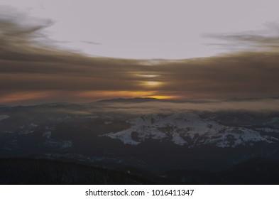 mystic winter landscape of mountain and sunset or sunrise. Ceahlau, Romania