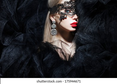 mystic woman in mask and red lips looking at camera