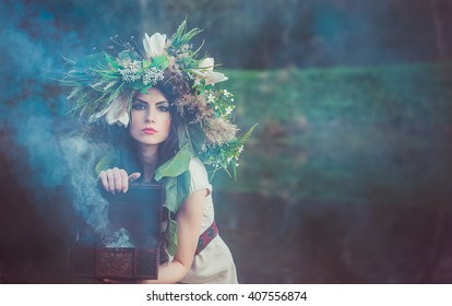 Mystic young girl with a wreath on his head and chest in the hands is in the swamp