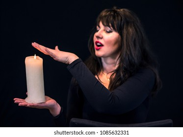 Mystic young women with candle on black background