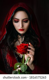 Mystical beautiful woman in a gothic costume of a medieval vampire in a hood. An adult girl holds a rose flower in her hands. Beautiful face red makeup, attractive lips. Halloween party image - Shutterstock ID 1816575263