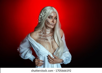 Mystical beautiful young blond woman with long ash gray hair posing image goddess death. Sexy vintage elegant dress. Creative makeup sugar skull. Wreath bride white flowers. Fiery red flaming backdrop