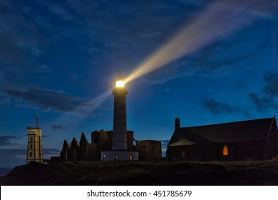 Mystical church and lighthouse illuminated over cloudy sky at Saint Mathieu point, Brittany, France