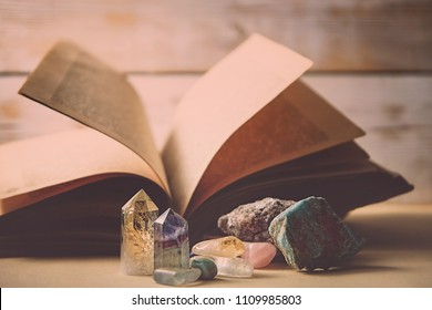 mystical composition with healing minerals and crystals and ancient book. the study of the properties of minerals and rocks, practice spells. Fabulous atmosphere. soft selective focus.