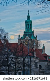 Mystical evening with full moon and cathedral belfry and roof tops in Europe Munich. Front cover or back cover of novel story book.Thriller background. Vampire werewolf ghost story concept. sky cloud.