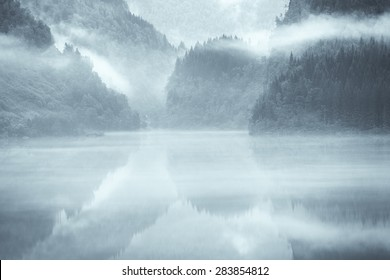 A mystical fjord in Norway with mountains and fog hanging over the water in a beautiful monochrome blue color.